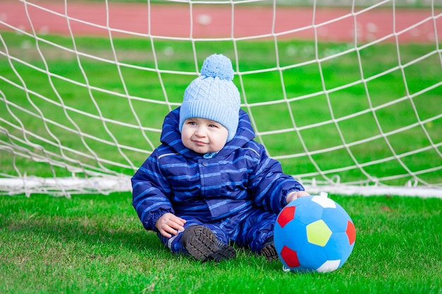 青いオーバーオールの赤ちゃんは、ゴールでサッカー場に座っています