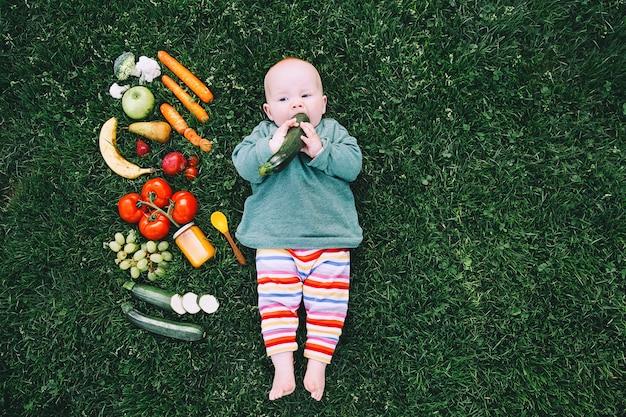 다채로운 옷을 입은 아기가 음식을 시도하고 푸른 잔디에 다양한 신선한 과일 채소를 틀고 있습니다