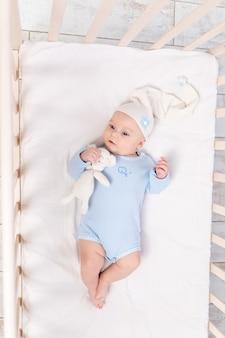 테디 베어 장난감이있는 침대에있는 아기가 잠자리에 들거나 아침, 가족 및 출생 개념에 일어났습니다.