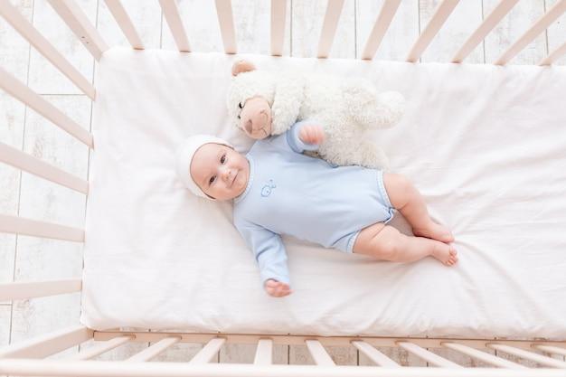 테디베어 장난감이 있는 유아용 침대에 있는 아기는 잠자리에 들거나 아침, 가족, 출생 개념에서 깨어납니다.