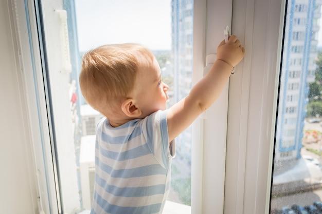 危険にさらされている赤ちゃん。小さな赤ちゃんが窓を開けようとしてハンドルを引っ張る