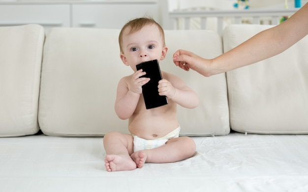 기저귀를 차고 침대에 앉아 스마트폰을 들고 있는 아기