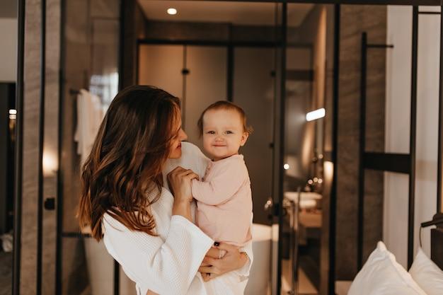 분홍색 점프 수트를 입은 아기는 엄마가 말을하는 동안 달콤하게 미소를지었습니다. 욕실의 배경에 아이와 함께 연주 흰색 목욕 가운에 장 발 아가씨.