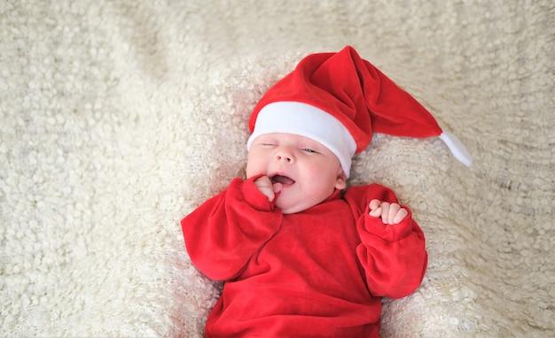 白い背景の上のサンタの衣装で赤ちゃん。サンタの帽子のクリスマスの幼児