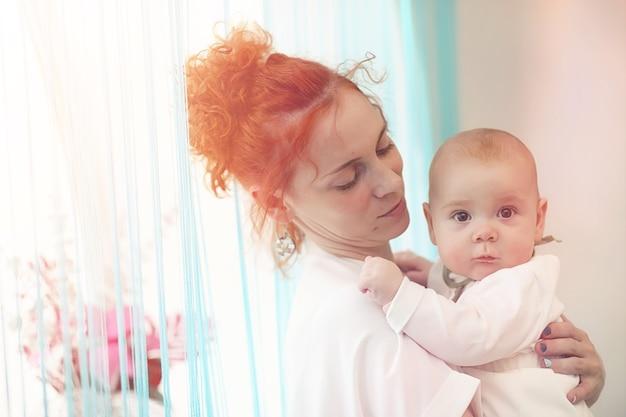女の子の腕の中で赤ちゃん。ママは子供を抱きしめています。小さな赤ちゃんと幸せな母親