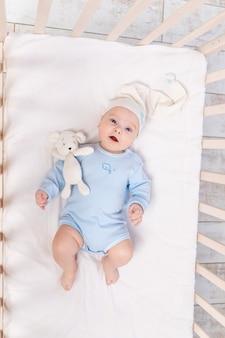 아침에 또는 자기 전에 집에 있는 아기 침대에 있는 아기, 가족과 출생의 개념