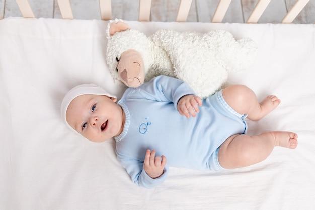 침대에있는 아기, 테디 베어 장난감, 어린이 및 출생 개념으로 누워있는 3 개월 아기 웃음
