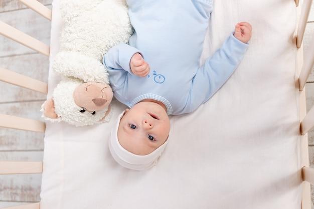 침대에있는 아기, 테디 베어 장난감, 어린이 및 출생 개념으로 침대에서 3 개월 귀여운 아기의 초상화