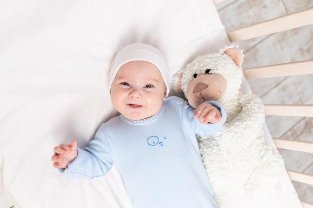 침대에있는 아기, 테디 베어 장난감, 어린이 및 출생 개념으로 침대에서 3 개월 웃는 아기의 초상화