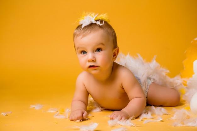 Ребенок в образе курицы с перьями и раковины на желтом пространстве изолировать, место для текста
