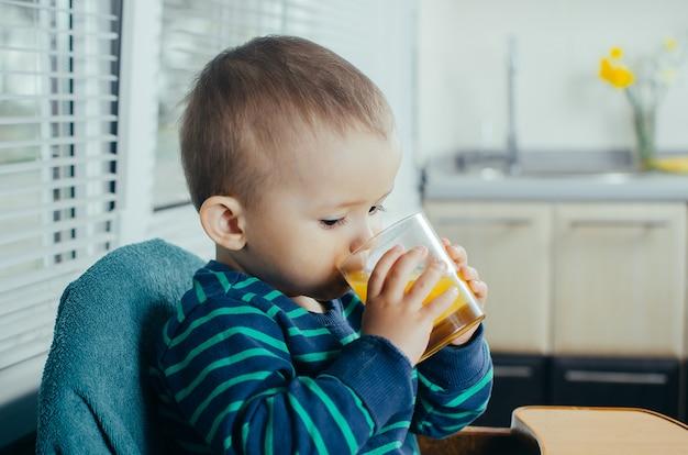 オレンジジュース、ビタミン、健康を飲んでいる台所の赤ちゃん