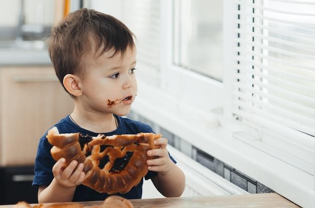 큰 롤빵 또는 초콜릿 파이를 먹고 부엌에서 아기 프리미엄 사진
