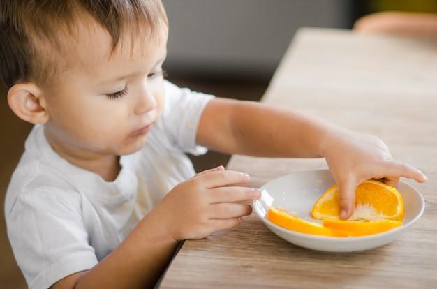 Ребенок на кухне в белой футболке берет дольку апельсина
