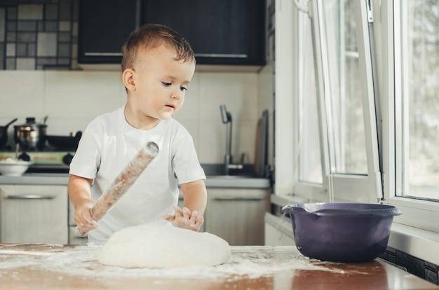 Малыш на кухне знает свое дело в процессе приготовления теста для выпечки