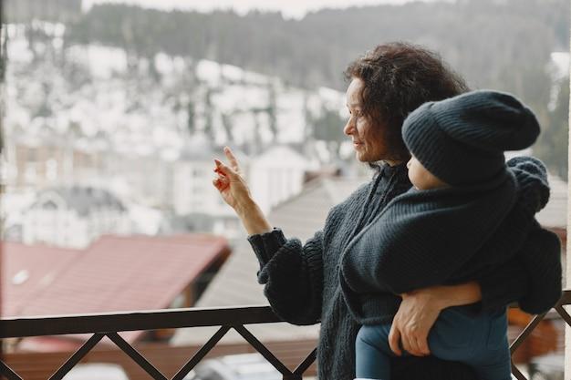 暖かい服を着た赤ちゃん。孫娘と一緒に立っている祖母。冬の山での休暇