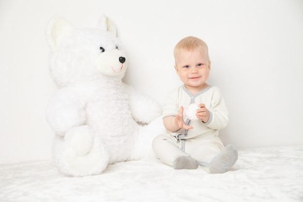 大きな白いテディベアと一緒に座って、白い背景の上のカメラを見ている白いスーツの赤ちゃん。