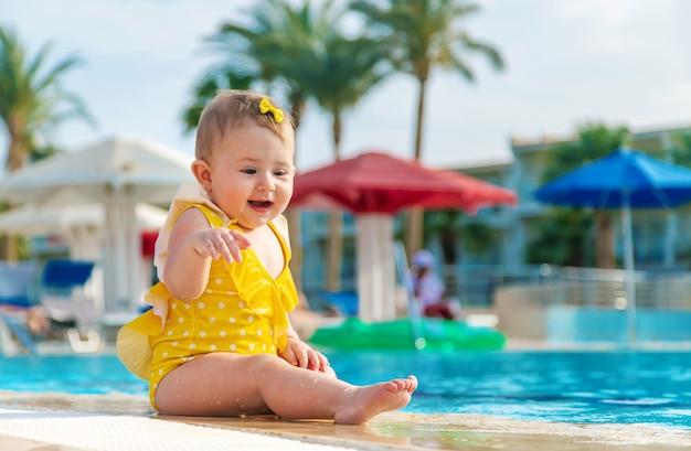 黄色い服を着た赤ちゃんがプールのそばに座って微笑む