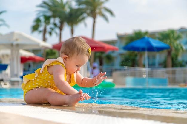 黄色い服を着た赤ちゃんがプールのそばに座って水をはねかける