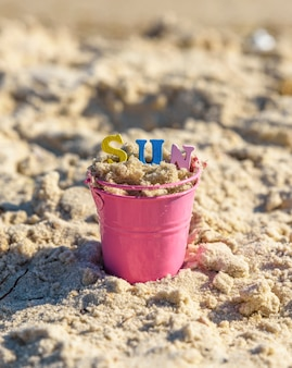 Baby iron bucket filled with wooden colorful letters, inscription sun