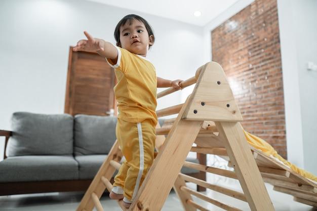 아기는 거실에 있는 피클러 삼각형 장난감을 타고 올라가면서 도움을 청하는 것을 두려워합니다.