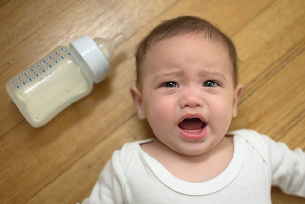 Baby is crying on the floor with the formula bottle