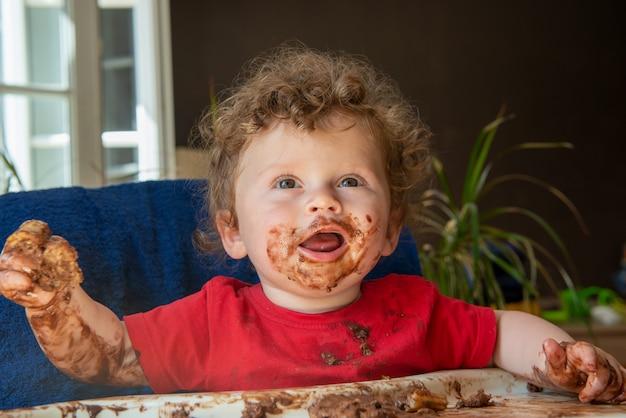 아기는 초콜릿 케이크를 먹고있다
