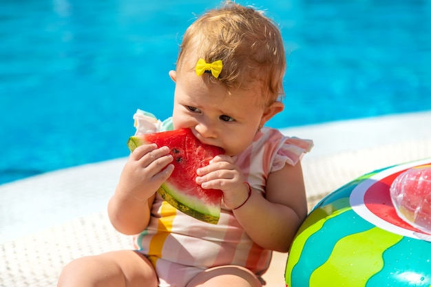 아기가 수영장 옆에서 수박을 먹고 있습니다. 선택적 초점입니다. 어린이.