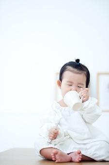 아기는 흰색 테이블에 이유식을 먹고있다.