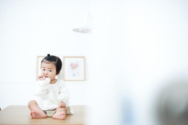 아기는 흰색 테이블에 자신의 이유식을 먹고있다.