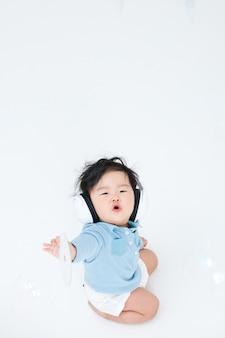 아기는 그의 헤드폰에서 음악을 듣고 즐기고있다.