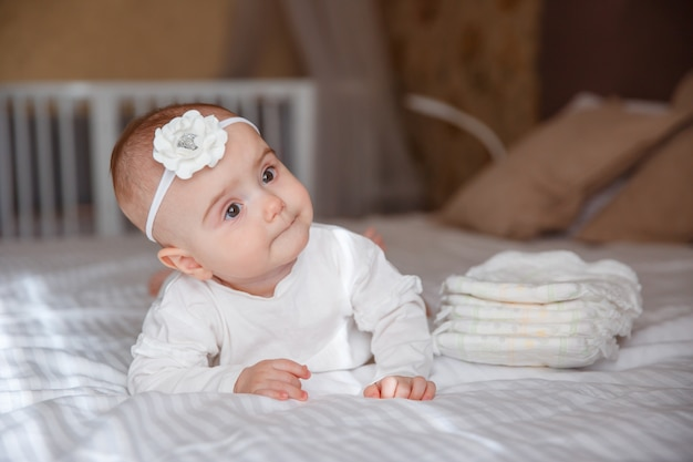 The baby is lying on the bed in the bedroom , a stack of diapers