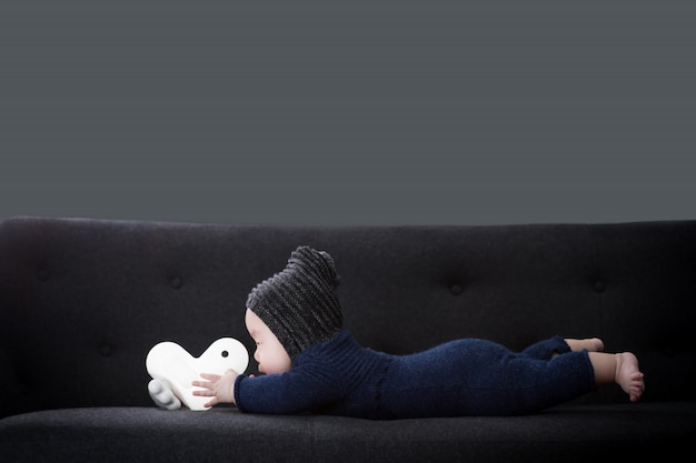 The baby is lying on the black sofa and holding the doll.
