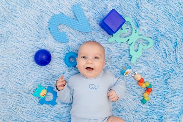 赤ちゃんはおもちゃの中で自宅の青いマットの上に横たわっています
