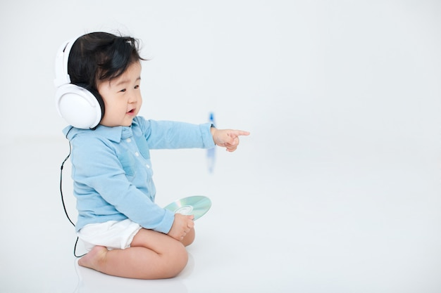 Baby is playing happily with his headphones on white