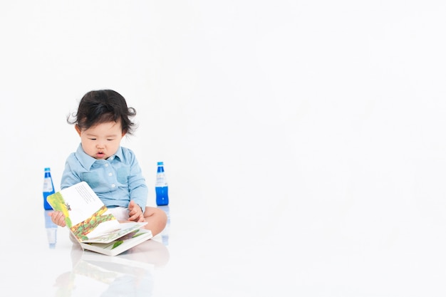 The baby is reading a book on a white room.
