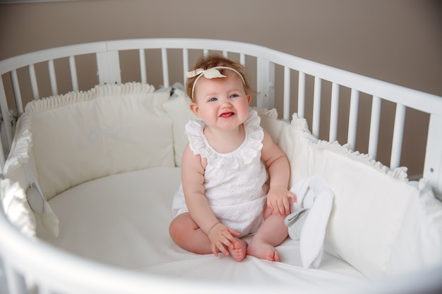 The baby is sitting in the crib in the bedroom smiling