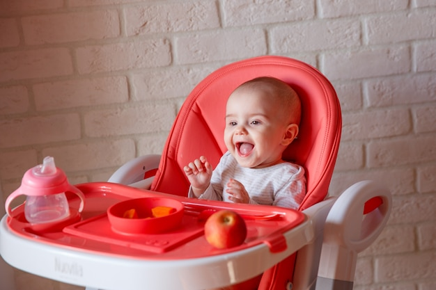The baby is sitting in a high chair eating