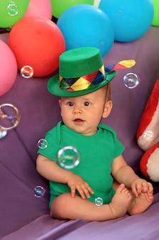赤ちゃんは風船で楽しいお祭りの雰囲気の中で座って、シャボン玉を見ています。
