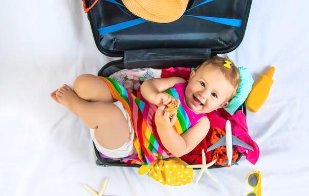 赤ちゃんはスーツケースに座って、旅行の準備をしています