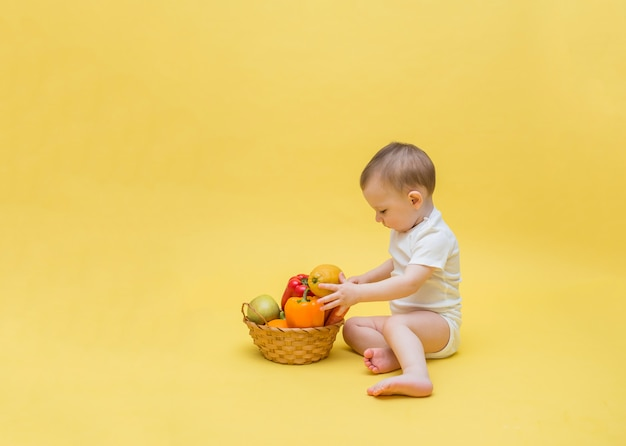 The baby is sitting with a basket of vegetables and fruits. the baby is sorting through a basket of vegetables and fruit on a yellow space. copy space