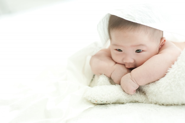 The baby is staring at the front on a white bed with a white background.