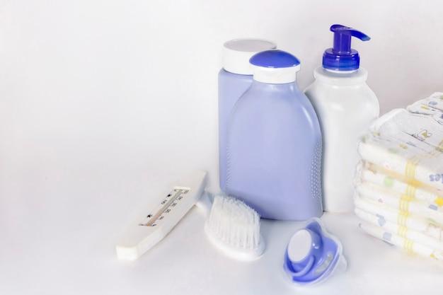 목욕을 위한 아기 용품:샴푸, 비누, 가루, 빗, 수온계, 젖꼭지, 흰색 배경에 기저귀 더미. 아기 세척 액세서리. 아기 돌보기. 공간을 복사합니다.