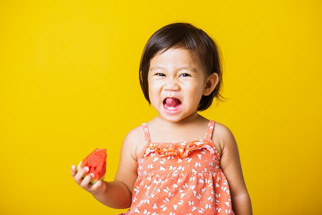Baby or kid cute little girl attractive laugh smile wearing t-shirt playing holds cut watermelon fresh for eating