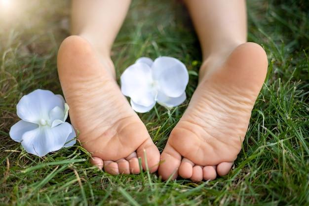 Малыш лежал на траве в парке летом, детские ножки крупным планом