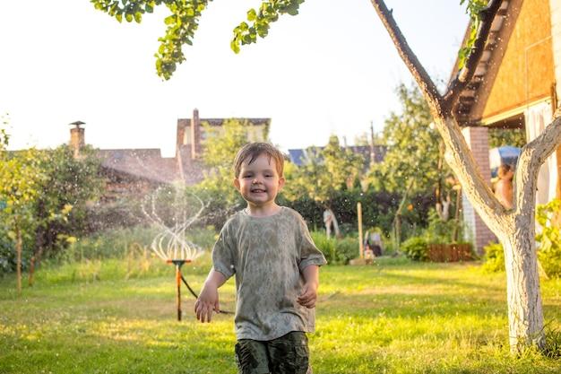 Малыш, пока они играют с водяной тростью в саду. концепция: свобода, счастье, свободное время.