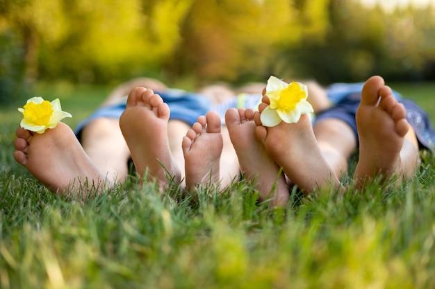 Детские дети лежат на траве в парке летом, детские ножки крупным планом