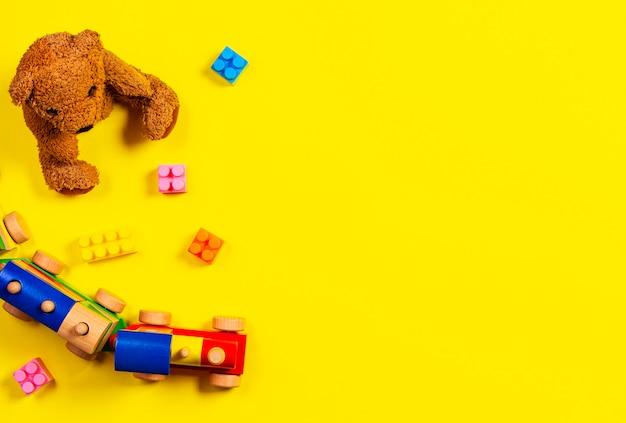 赤ちゃんの子供のおもちゃの背景。テディベア、木製の電車、黄色の背景にカラフルなブロック