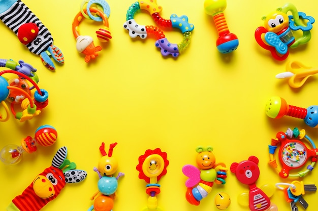 Baby kids toys on yellow background. top view