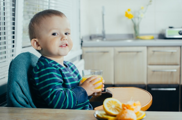 Baby in the kitchen drinking orange juice, vitamins and health