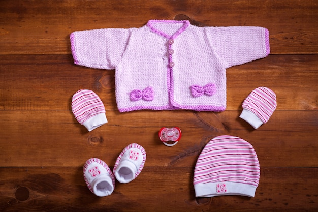 Baby knitted clothes set on brown wooden table, top view, flat lay